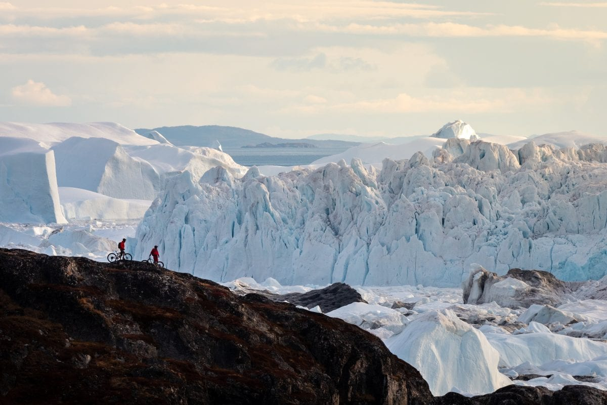 It's hard to take in the scale of the massive icebergs coming from the Sermeq Kujalleq Glacier and out into the ocean through the Ilulissat Icefjord.  Here, a pair of mountain bikers contemplate their magnitude.  Ilulissat, West Greenland.  Riders: Chris Winter, Ryan Stuart.  Photo: Ben Haggar @benhaggarphoto benhaggar.com
