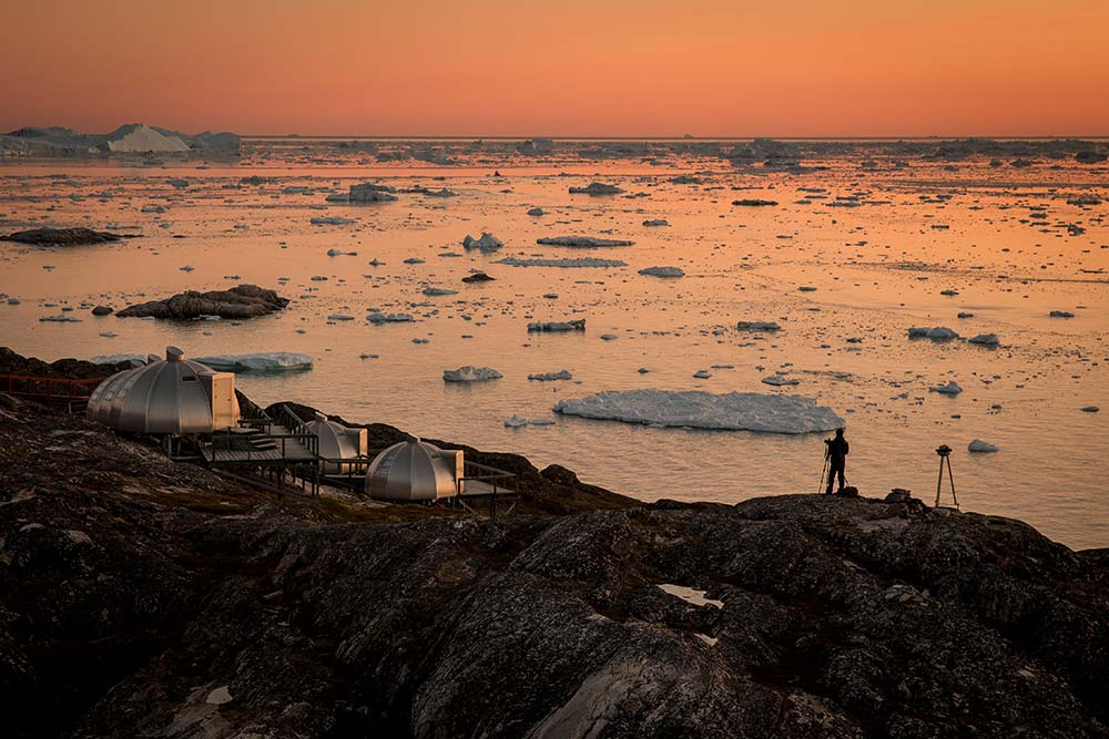 A Photographer In The Sunset Near Hotel Arctic In Ilulissat In Greenland