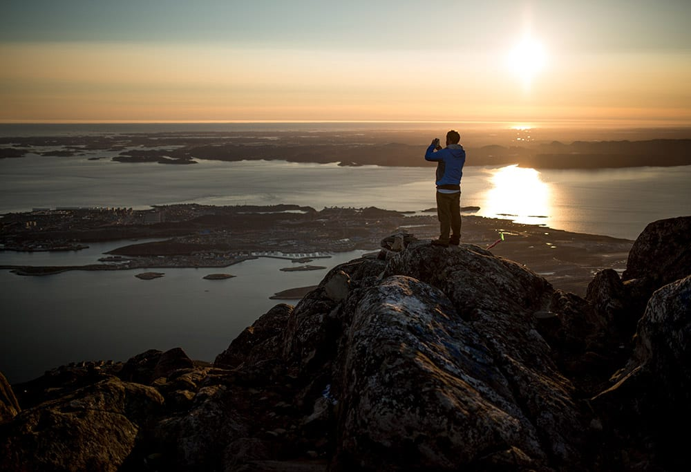 A Hiker Photographing Nuuk From The Peak Of Store Malene Ukkusissaq In Greenland