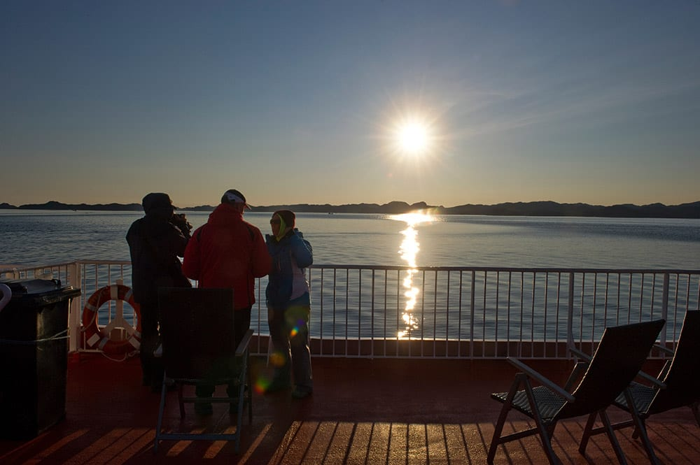 Tourist On The Upper Deck Of Sarfaq Ittuk Under The Midnight Sun In Greenland